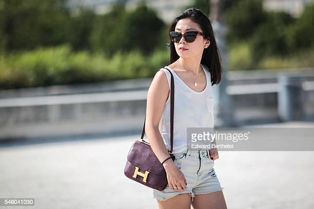 May Berthelot is wearing a The Kooples top an Iro short Asos sandals a Hermes Constance bag sunglasses and a necklace from Nine Avril Paris during a...
