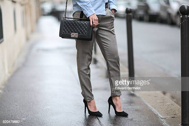May Berthelot is wearing a Topshop blue shirt The Kooples gray pants Bash black heels and a black Chanel boy bag during a street style session on...