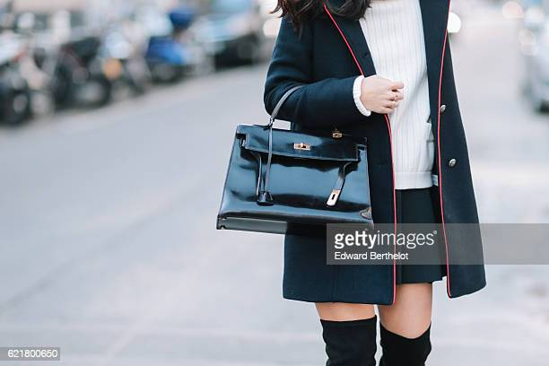 May Berthelot is wearing a Zara dark blue coat with red lines a Chanel white turtleneck sweater Topshop black skirt Zara thigh high black boots and a...