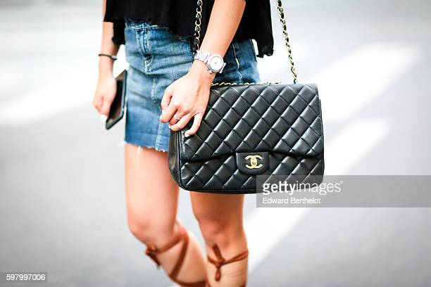 May Berthelot is wearing an Asos black top Asos brown sandals lace up leg a Maje blue denim jeans skirt and a Chanel jumbo bag on August 30 2016 in...