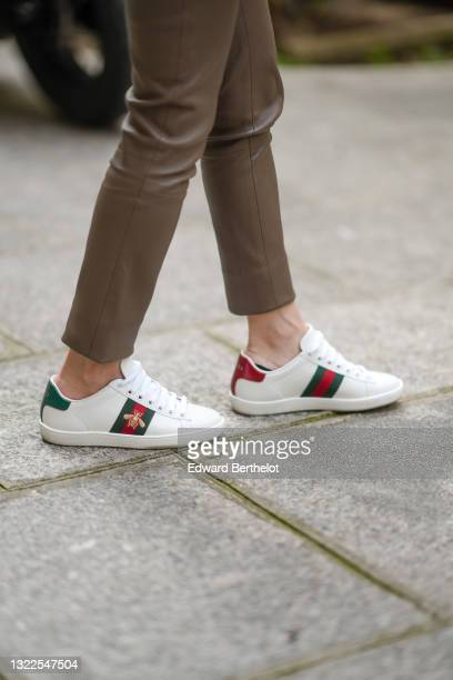 May Berthelot @may.berthelot wears a brown shiny leather pants, white leather Ace sneakers from Gucci with red green and gold embroidery logo, on May...