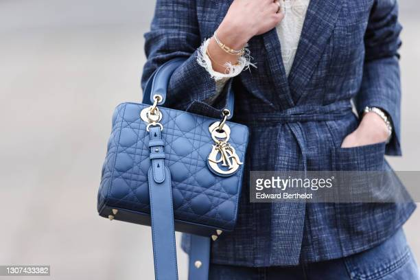 May Berthelot @may.berthelot wears a white ruffle mesh top with floral embroidery from Dior, a blue blazer jacket with a belt from Dior, a blue...