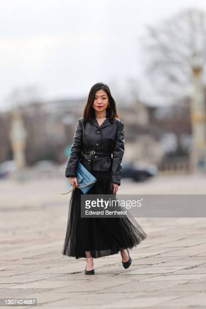 May Berthelot @may.berthelot wears earrings, a golden Dior necklace, a black leather jacket from Dior, a Dior belt, a blue Dior bag, a black mesh...