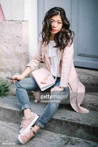 May Berthelot wears a New Look pink trench coat a Chanel brooch an Ame Moi pink bag New Look sneakers Zara jeans and a New Look white lace top in Rue...