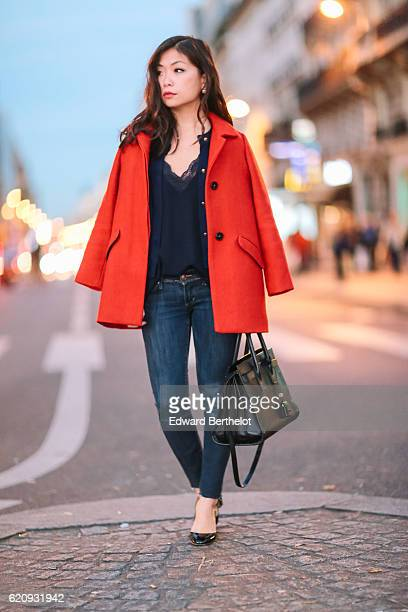May Berthelot wears a Zara red coat a Zara black lace top The Kooples blue denim jeans a Saint Laurent bag 'Sac de Jour' and Valentino Tango shoes on...