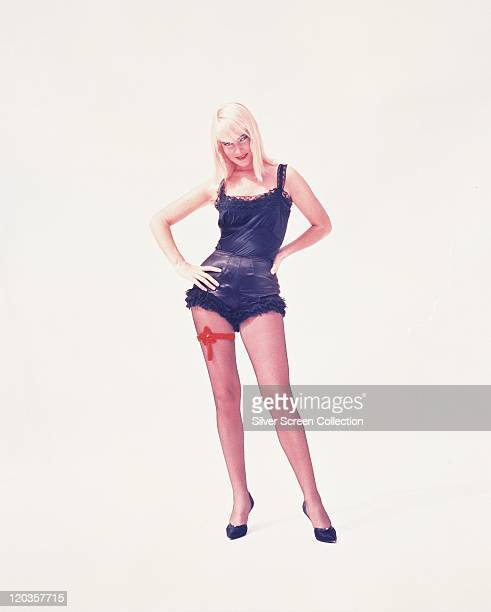 May Britt Swedish actress wearing a black camisole and black frilly knickers with a red ribbon tied around her right leg in a studio portrait against...