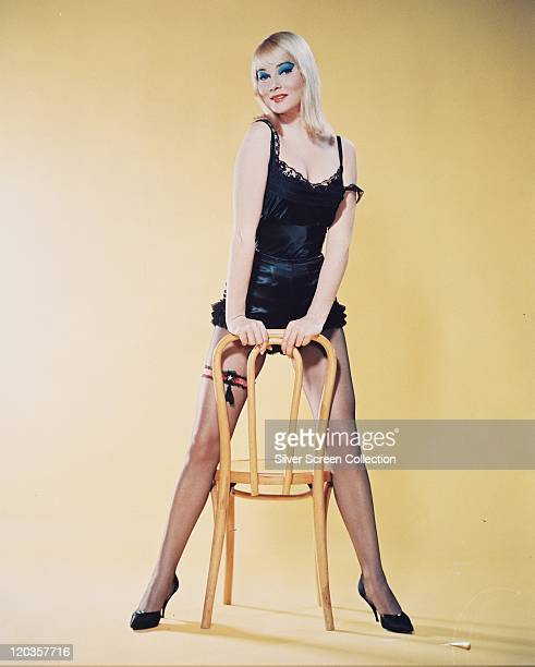 May Britt Swedish actress wearing a black camisole and black frilly knickers posing leaning against a chair in a studio portrait against a yellow...