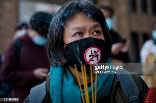 May Chiu, one of the organizers of the protest, lights incense during a vigil following a demonstration against anti-Asian racism in Montreal,...