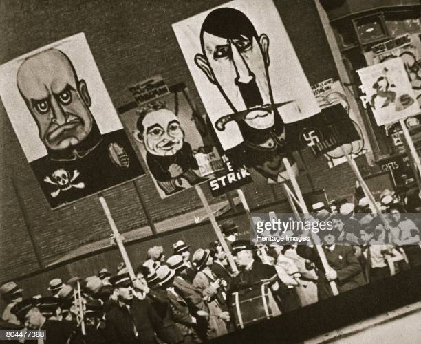May Day parade East Fourteenth Street near Union Square New York USA early 1930s Marchers holding up placards with satirical portraits of Benito...