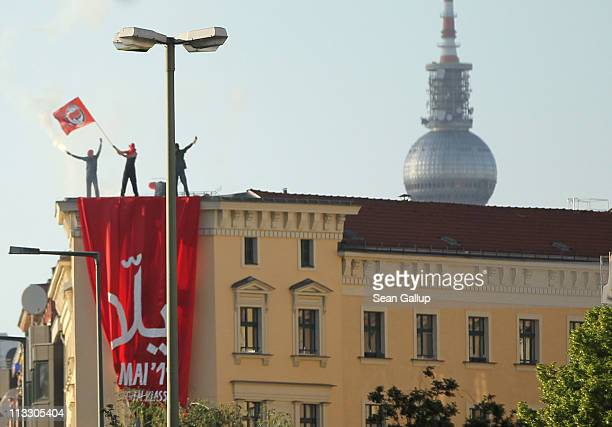 May Day protesters wave a flag on the roof of a building in the district of Kreuzberg on May 1 2011 in Berlin Germany May Day demonstrations are...