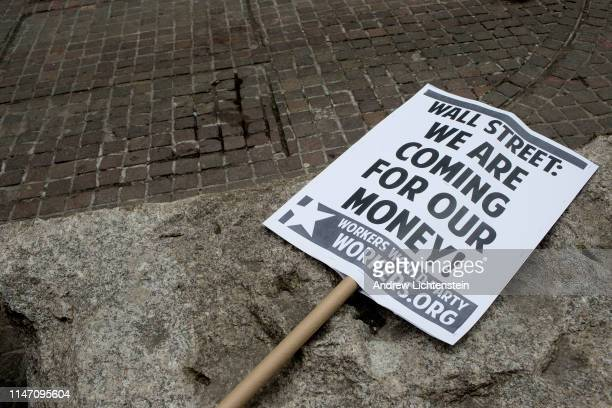 May Day sign decorates a concrete barrier before a demonstration on May 1, 2019 at Wall Street in New York City.
