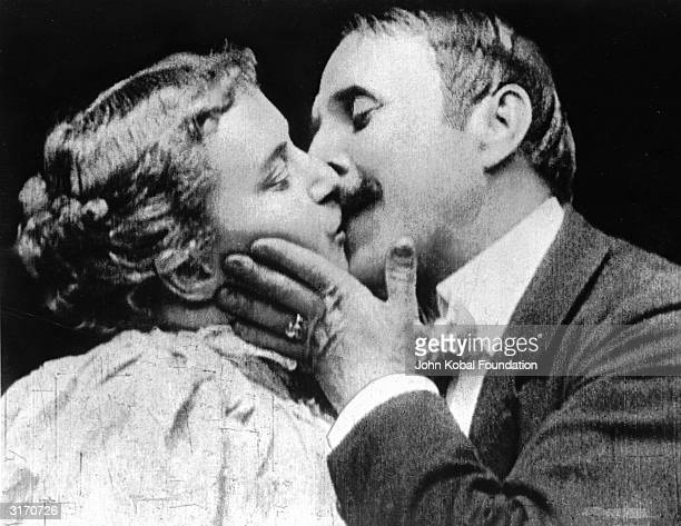 May Irwin and John C Rice stars of the Broadway play 'The Kiss' reenact the play's famous kissing scene for the Edison Company's cameras The film...