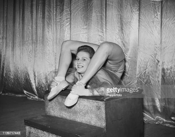 May Lewis a 19 year old contortionist and one of Gordon Roy's Peach Girls wraps her heels over her head during an acrobatic act on stage at a theatre...
