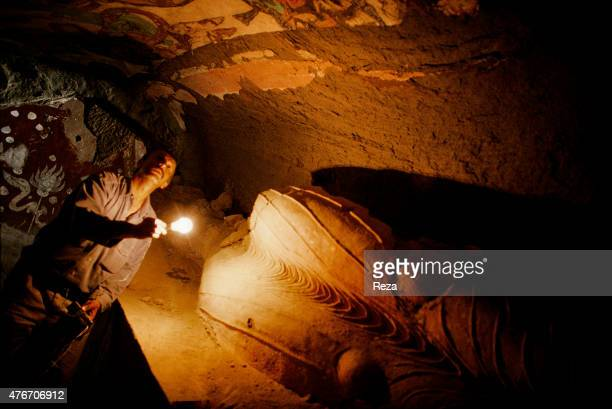 May Thousand Buddha caves Kyzyl Xinjiang Eastern Turkestan China Holding a light bulb photographer Reza is leaning over the remains of a Buddha...