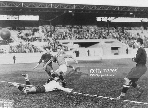 A player kicking the ball whilst being tackled in the match between Egypt and Portugal in the Football event during the 1928 Olympic Games in...