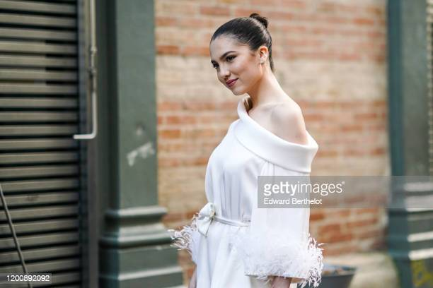 Maya Henry wears earrings a white oneshoulder top with cuffs decorated with feathers outside Ralph Russo during Paris Fashion Week Haute Couture...