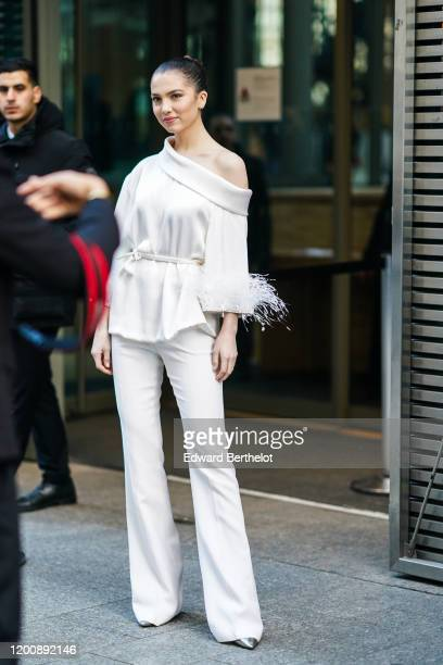Maya Henry wears earrings a white oneshoulder top with cuffs decorated with feathers white fulllength flare pants outside Ralph Russo during Paris...