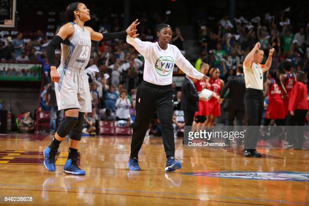 Maya Moore and Alexis Jones of the Minnesota Lynx give high fives during the game against the Washington Mystics in Game One of the Semifinals during...