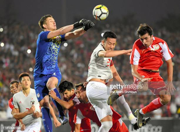 Maya Yoshida of Japan and Rustam Yatimov of Tajikistan compete for the ball during the FIFA World Cup Asian Qualifier second round Group F match...