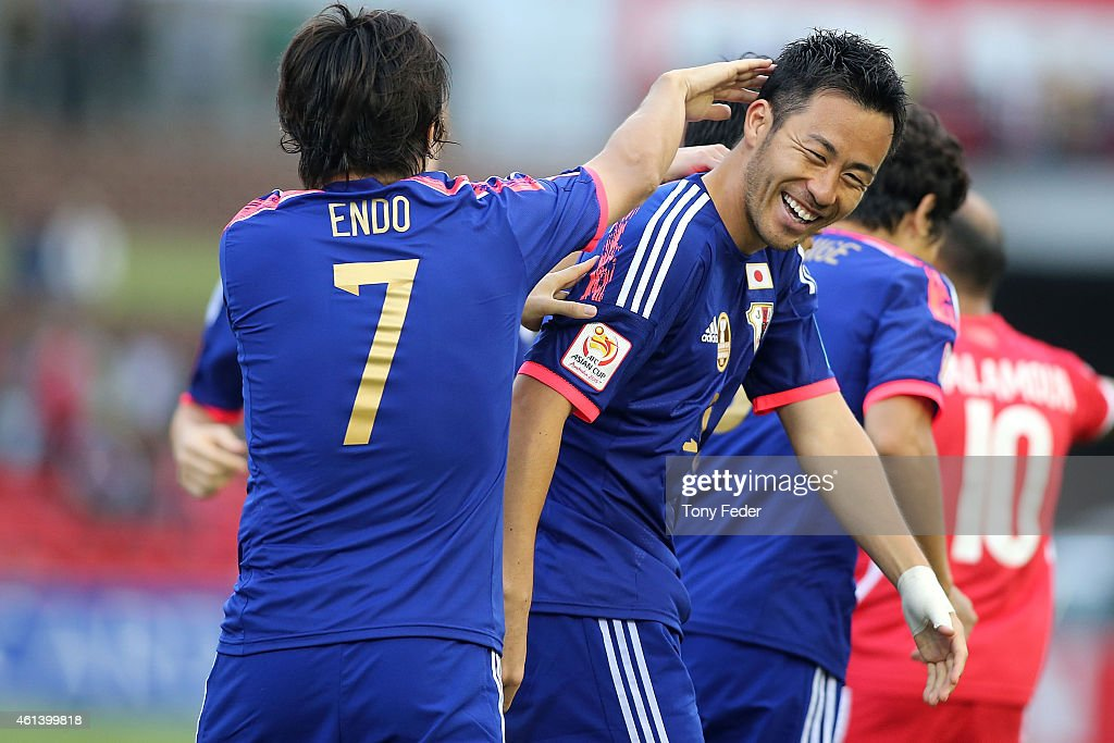 Maya Yoshida of Japan celebrates scoring his team's fourth goal with team mate Yasuhito Endo during the 2015 Asian Cup match between Japan and Palestine at Hunter Stadium on January 12, 2015 in Newcastle, Australia.