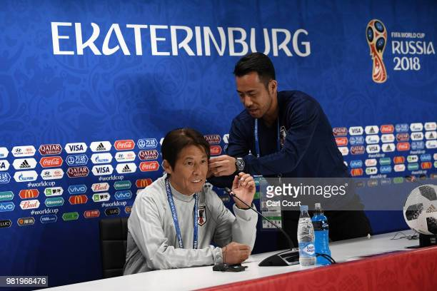 Maya Yoshida of Japan helps Akira Nishino Manager of Japan with his earpiece in a press conference ahead of the FIFA World Cup Group H match between...