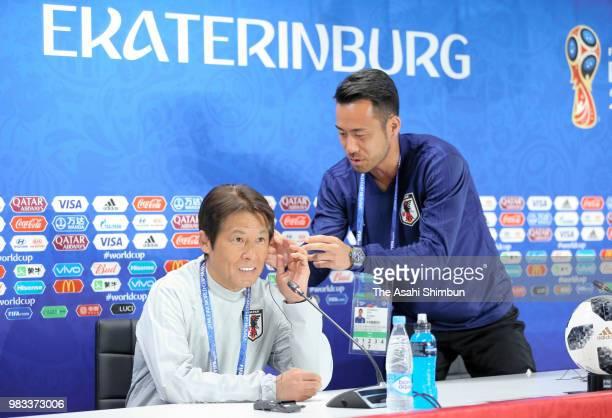 Maya Yoshida of Japan helps head coach Akira Nishino wearing an earpiece prior to a press conference ahead of the 2018 FIFA World Cup match against...