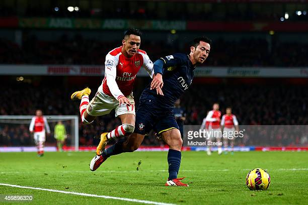 Maya Yoshida of Southampton challenges Alexis Sanchez of Arsenal during the Barclays Premier League match between Arsenal and Southampton at Emirates...