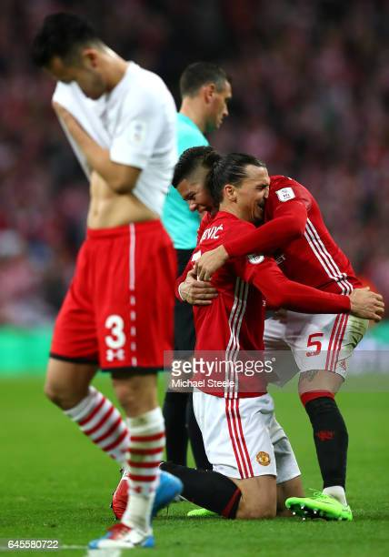 Maya Yoshida of Southampton looks dejected as Zlatan Ibrahimovic and Marcos Rojo of Manchester United celebrate victory after the EFL Cup Final match...
