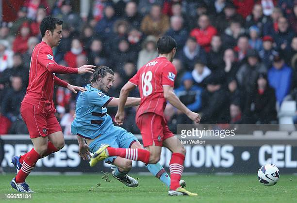 Maya Yoshida of Southampton tries to tackle Andy Carroll of West Ham during the Barclays Premier League match between Southampton and West Ham United...