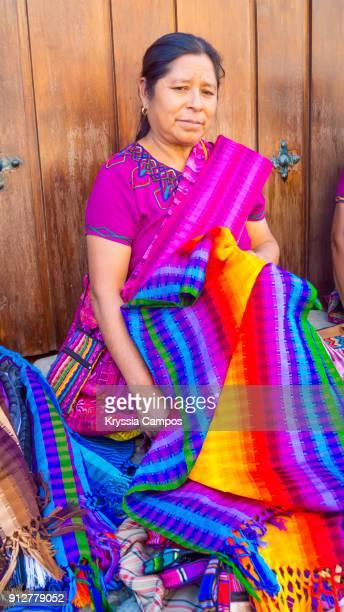Mayan woman sitting at streets of Antigua, selling handmade textiles and souvenirs, Guatemala