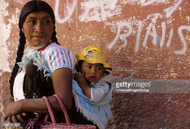 A Mayan woman with braided hair carries her baby on her back in front of a grafitti painted wall in San Cristobal de las Casas ChiapasMexico