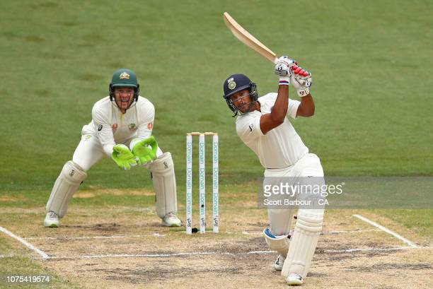 Mayank Agarwal of India hits a six as wicketkeeper Tim Paine of Australia looks on during day four of the Third Test match in the series between...
