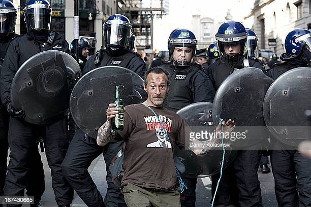 Mayday anti-capitalist protestor mocking the police during the city of london riots. Police officers in riot gear.