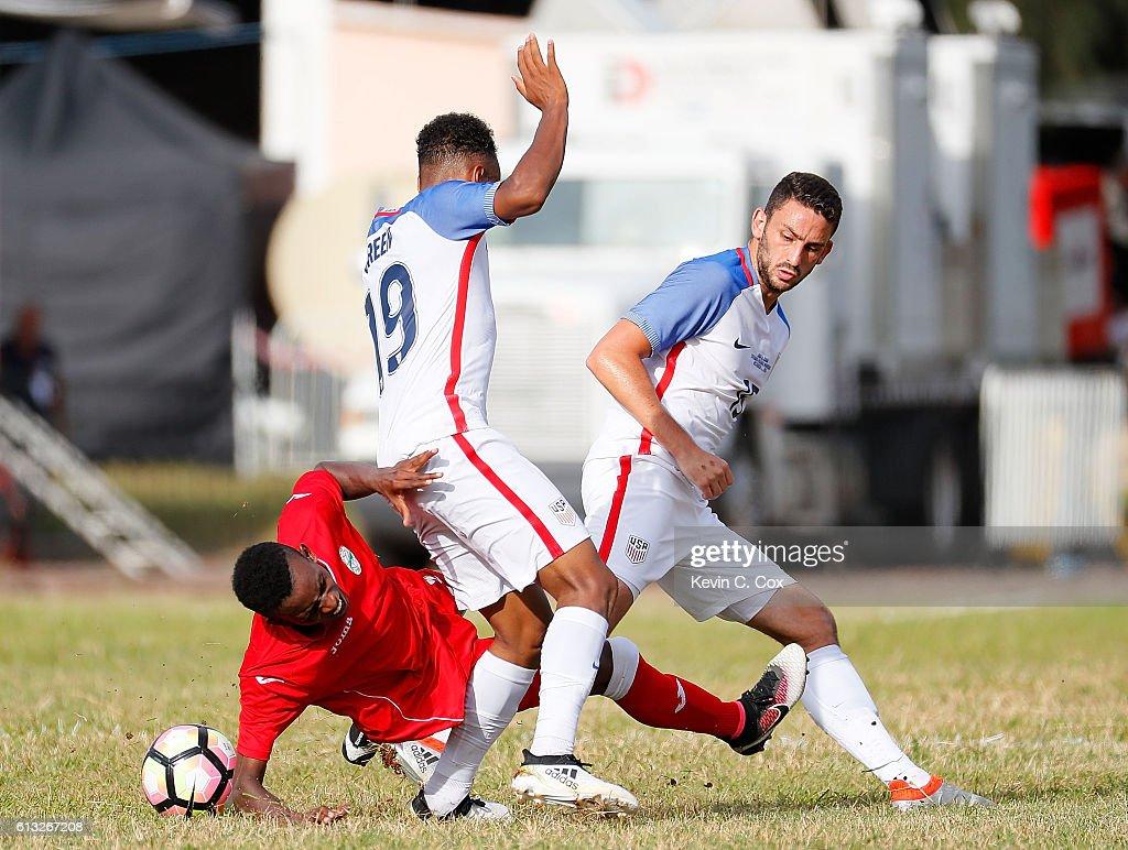 Maykel Reyes Ascuy #9 of Cuba falls as he battles against Julian Green #19 and Steven Birnbaum #15 of the United States at Estadio Pedro Marrero on October 7, 2016 in Havana, Cuba.