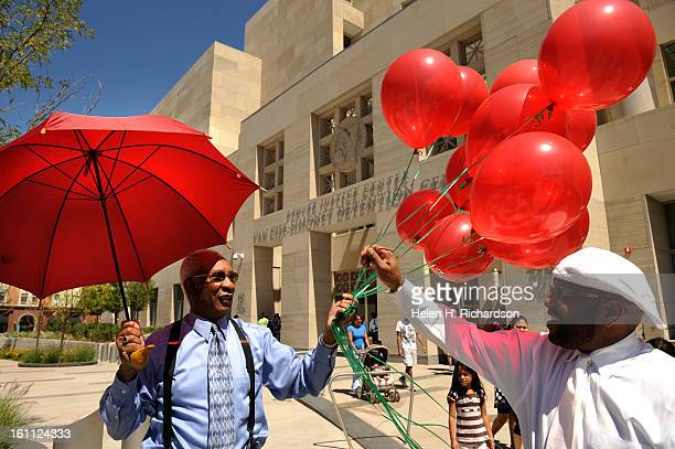Maynard Hampton left hands out red balloons to church member and rally supporter Ronald Bullock right before the rally Rally members chose red green...