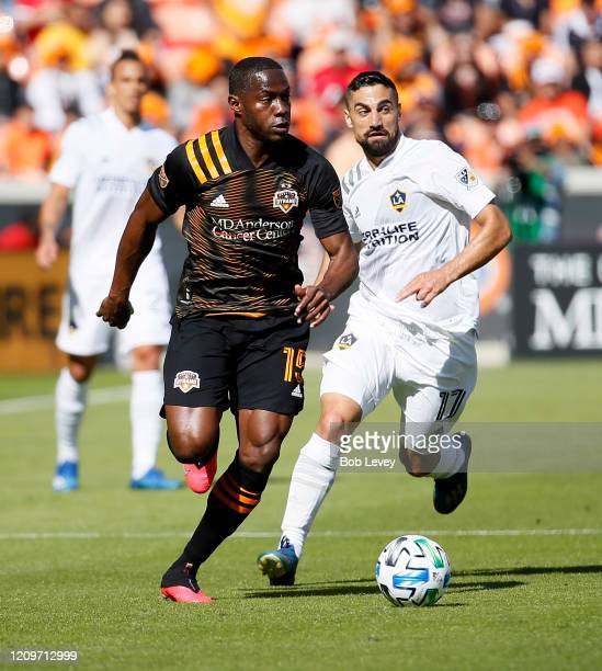 Maynor Figueroa of Houston Dynamo brings the ball up the field as Sacha Kljestan of Los Angeles Galaxy defends at BBVA Stadium on February 29 2020 in...