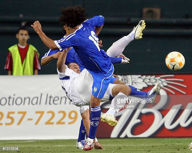 Maynor Morales of Guatemala flips over while kicking the ball away from Alexander Escobar of El Salvador during an international friendly match on...