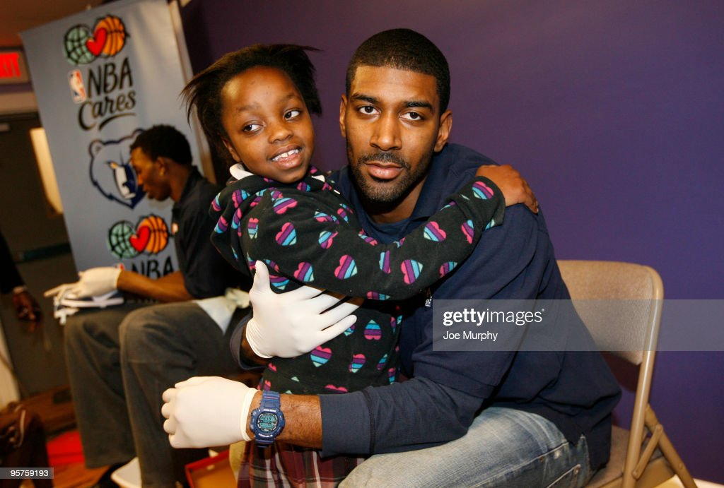 O.J. Mayo of the Memphis Grizzlies gives a young girl a hug after fitting her with new sneakers during a Samaritan's Feet shoe distribution on January 13, 2010 at Refugee Empowerment Program in Memphis, Tennessee.