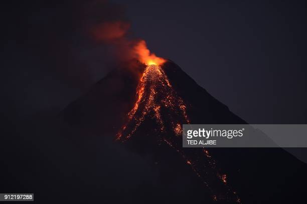 Mayon volcano emits lava cascading the slope as seen from Legazpi City in Albay province south of Manila on January 30 2018 The threat of...