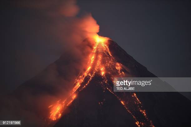 TOPSHOT Mayon volcano emits lava cascading the slope as seen from Legazpi City in Albay province south of Manila on January 30 2018 The threat of...