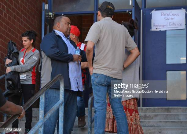 Mayor Daniel Rivera talks with people as they leave the emergency shelter at Arlington Middle school September 27 2019 in LAWRENCE Massachusetts