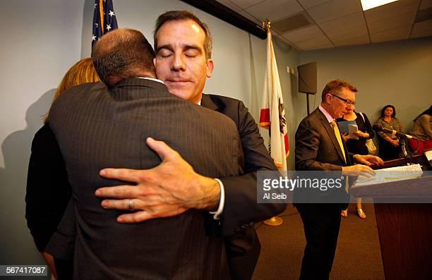 Mayor Eric Garcetti center hugs school board member Steve Zimmer left as he arrives with LAUSD Superintendent Dr John E Deasy right starting a press...