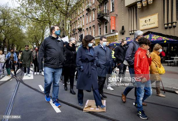 Mayor Femke Halsema walks along with victims' relatives and local residents in silence through De Pijp quarter in Amsterdam, on May 27, 2021. - A...
