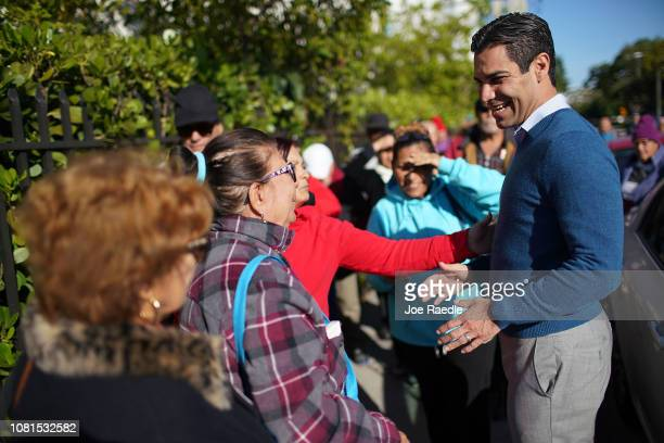 Mayor Francis Suarez greets people standing in line to receive their Christmas food at the 33rd annual food giveaway on December 12 2018 in Miami...