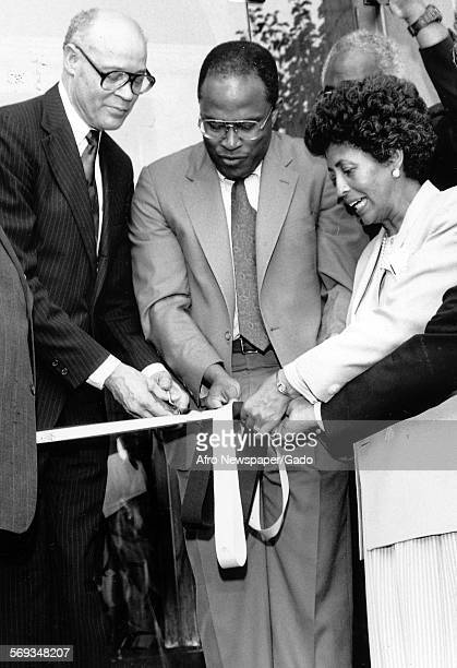 Mayor Kurt Schmoke and two other people cutting the ribbon to open the new National Fraternity House for Alpha Phi Alpha 1980