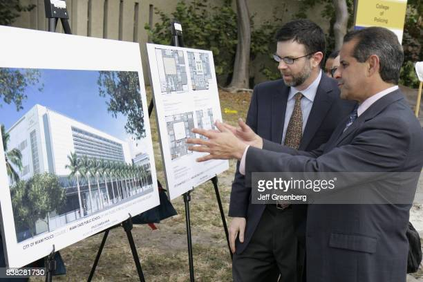 Mayor Manny Diaz looking at architectural rendering plans at the groundbreaking ceremony for the College of Policing