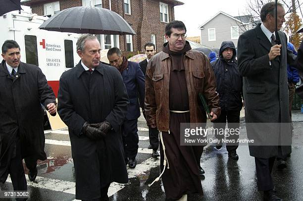 Mayor Michael Bloomberg a Franciscan friar and Gov George Pataki walk to St Francis' Church from the spot where American Airlines Flight 587 crashed...