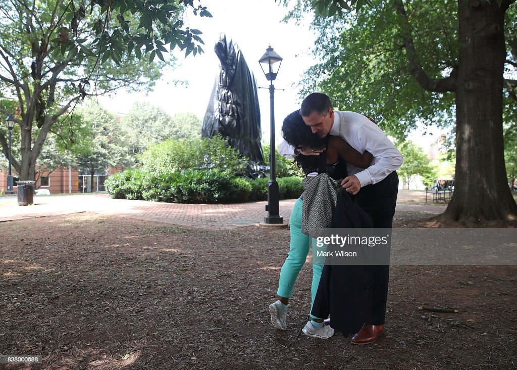 Mayor Mike Signer hugs life long resident Aaliyah Jones in front of the newly covered statue of Thomas Jonathan 'Stonewall' Jackson that stands in Justice Park, formerly known as Jackson Park, on August 23, 2017 in Charlottesville, Virginia. The Charlottesville city council voted unanimously to cover Confederate statues in black tarp.