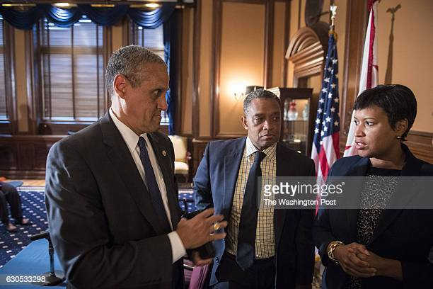 Mayor Muriel Bowser right US Attorney Channing Phillips left and DC Attorney General Karl Racine OAG center talk to a reporter after a signing to...