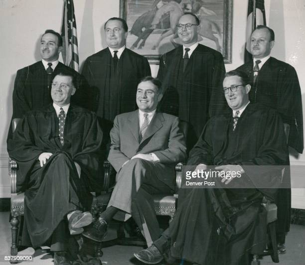 Mayor Newton poses with municipal court judges who have joined judges of other courts located in Denver in wearing black robes in court Seated and...